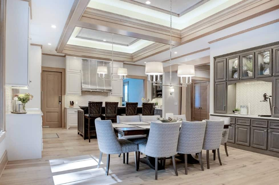 A dine-in kitchen with a modish dining table and chairs set situated on the hardwood flooring. The home also boasts a tray ceiling.