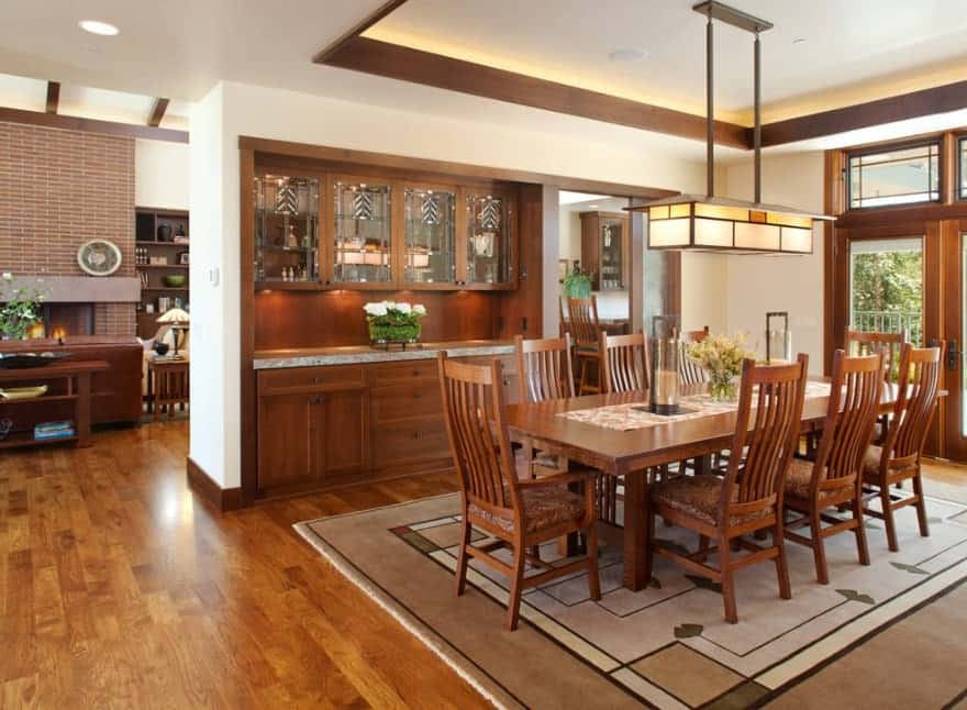 A classy dining table set on top of a rug covering the hardwood flooring. The room also has a tray ceiling.