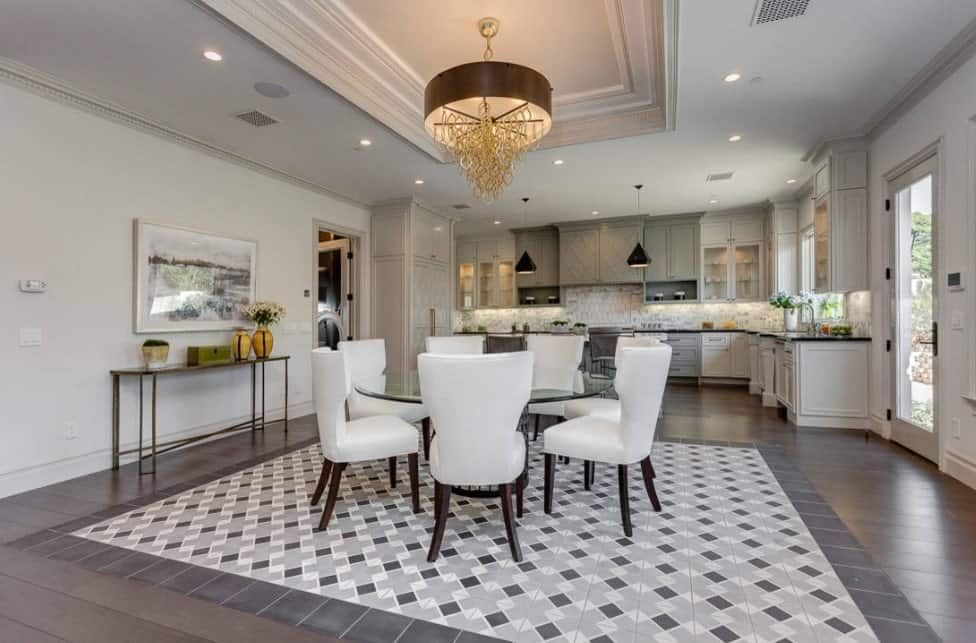 Spacious dine-in kitchen featuring hardwood flooring topped by a rug. The round dining table set is situated under the tray ceiling lighted by a beautiful chandelier.
