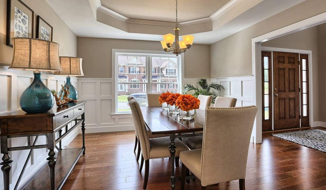 A dining room featuring hardwood flooring and a tray ceiling. The dining table is paired with modish chairs.