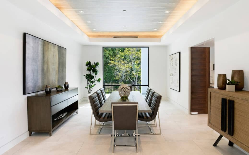 This dining room offers a dining table with modern seats set on the tiles flooring and is surrounded by white walls and a tray ceiling.