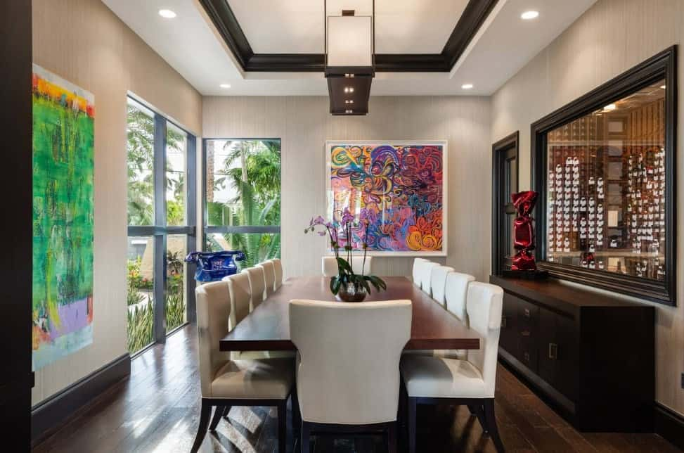 Modern formal dining room offering a rectangular dining table paired with white chairs set on the hardwood flooring.