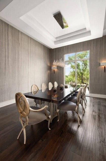 Formal dining room featuring stylish gray walls lighted by wall sconces along with hardwood flooring and a tray ceiling.