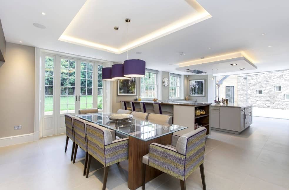 A dine-in kitchen featuring a glass top table with charming chairs lighted by stylish pendant lights on a tray ceiling.