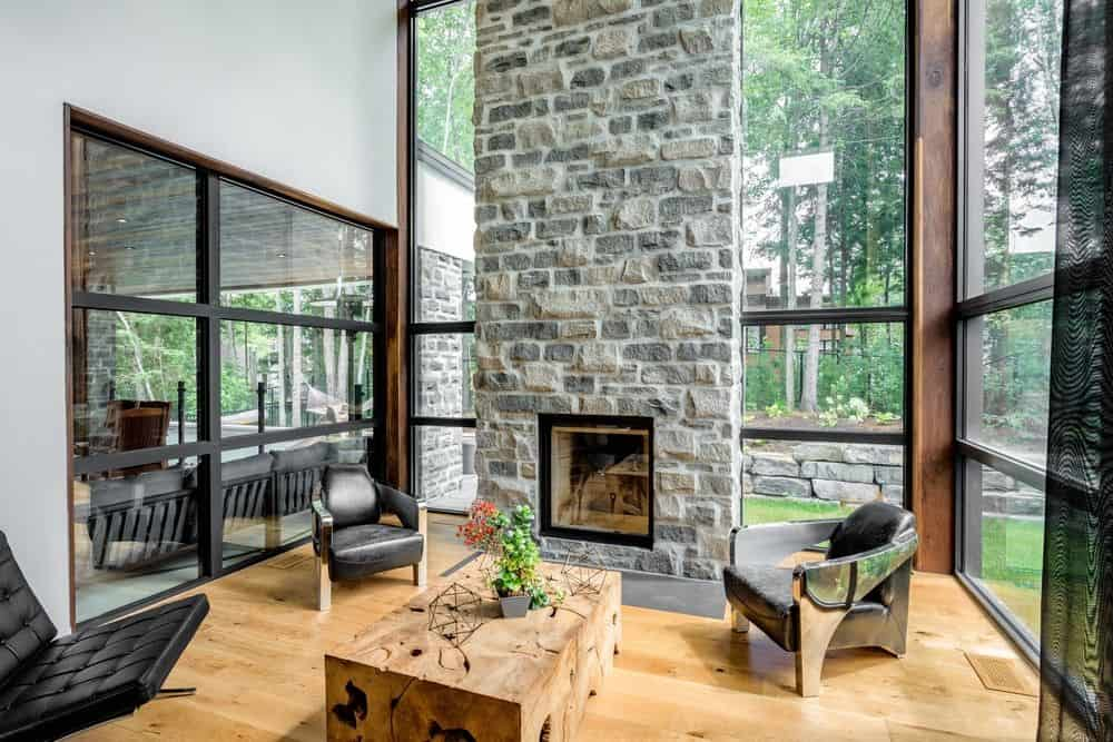 The glazed walls invite plenty of natural light in this high ceiling interior. It has metallic and leather chairs adding a sleek modern tone in the house.