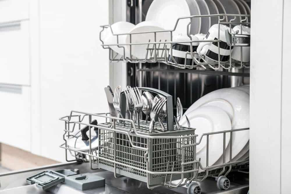 An open dishwasher with clean crockery.