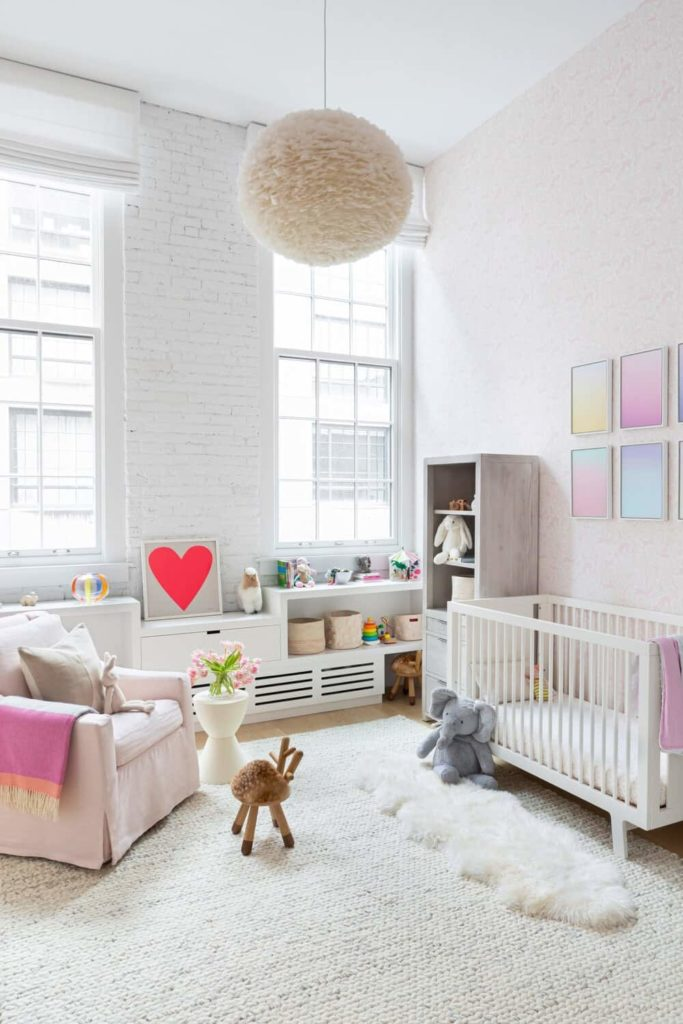 A nursery room featuring a lovely baby crib and a white area rug. There's a freestanding shelf on the side, along with colorful framed wall decors on the wall. The room is lighted by a fancy ceiling light.