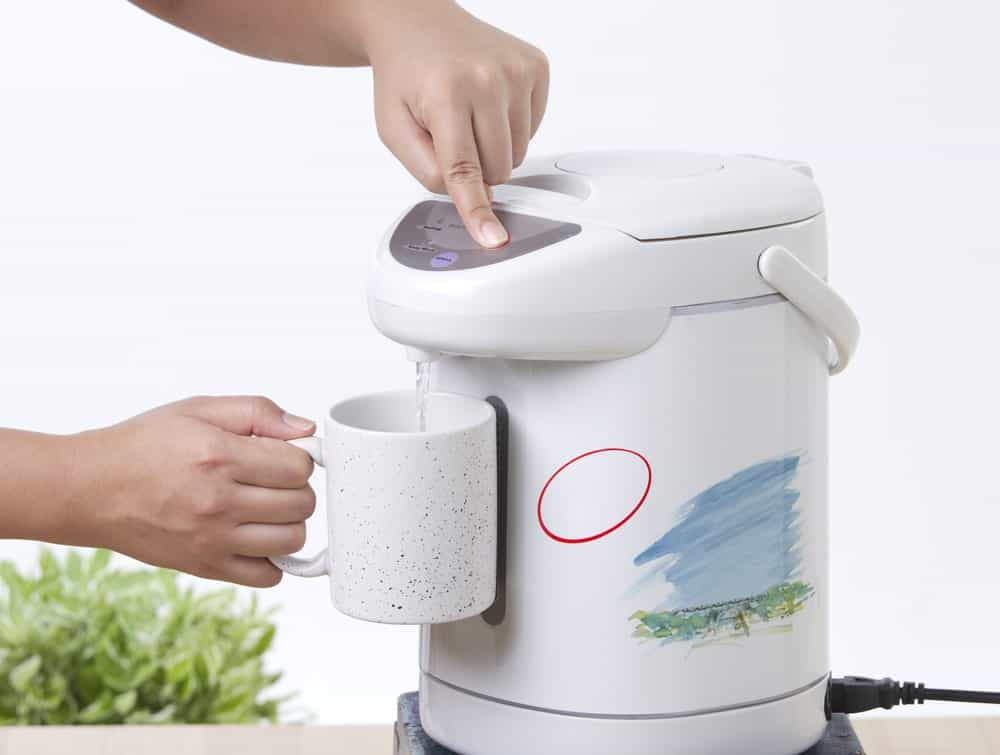 Pressing the electric water boiler for a cup of hot water.