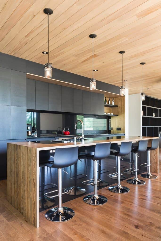 This kitchen offers an island bar aligned with black counter stools that complement the black cabinetry. It is illuminated with pendant lights that hung from a shiplap ceiling.