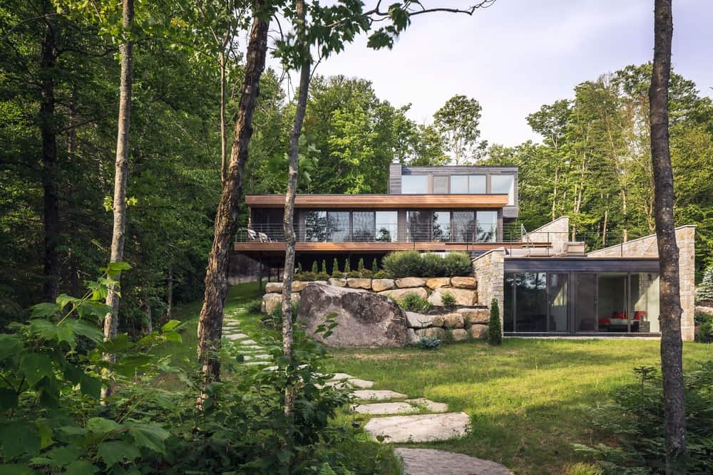 Attractive contemporary house covered with greeneries, featuring flagstone walkway and a huge rock with small stone accent wall.