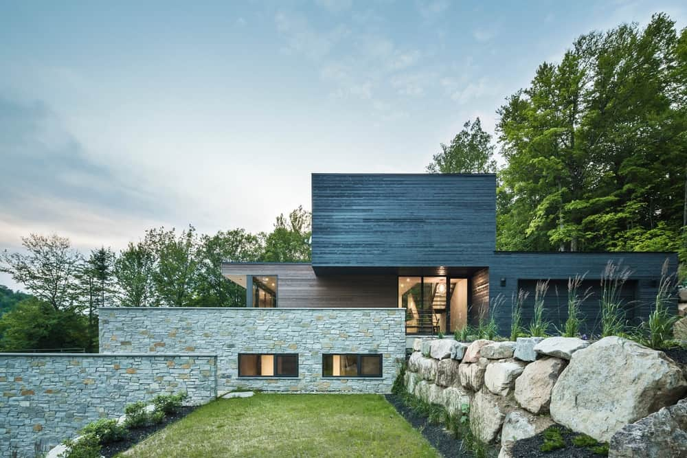 A captivating modern house with wood and brick walls featuring a marvelous large-rock retaining wall and a grass lawn. Trees on the background added a tranquility vibe on this place.