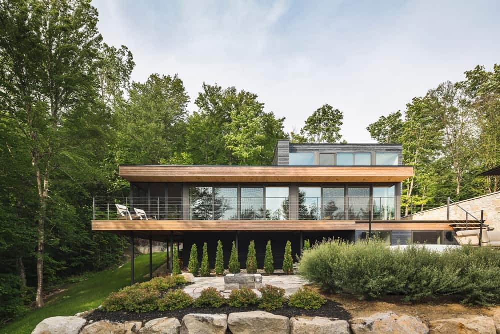 Closer look of the house with small pine trees and plants atop the rock wall creating a continuity look of this contemporary place.