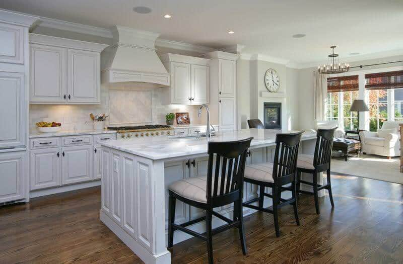 A beautiful cottage kitchen featuring white cabinets, tiled backsplash, hardwood flooring and a breakfast island with marble countertop and three wooden chairs with cushion.