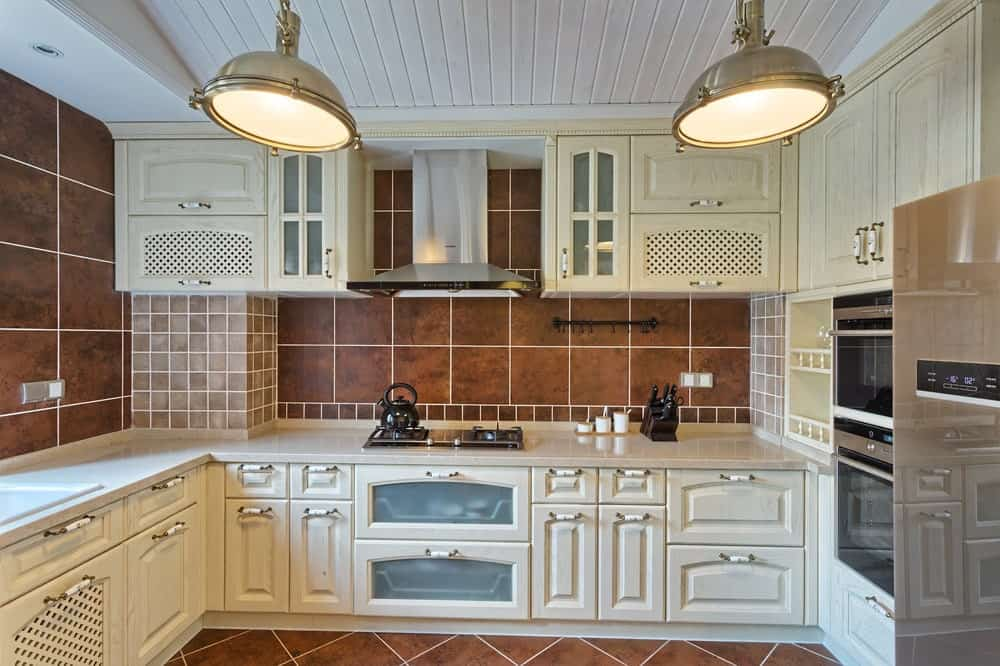 A classic kitchen with brown tiled walls and floors, two enormous pendant lights hanging on a white vaulted ceiling, white cabinets and stainless steel appliances.