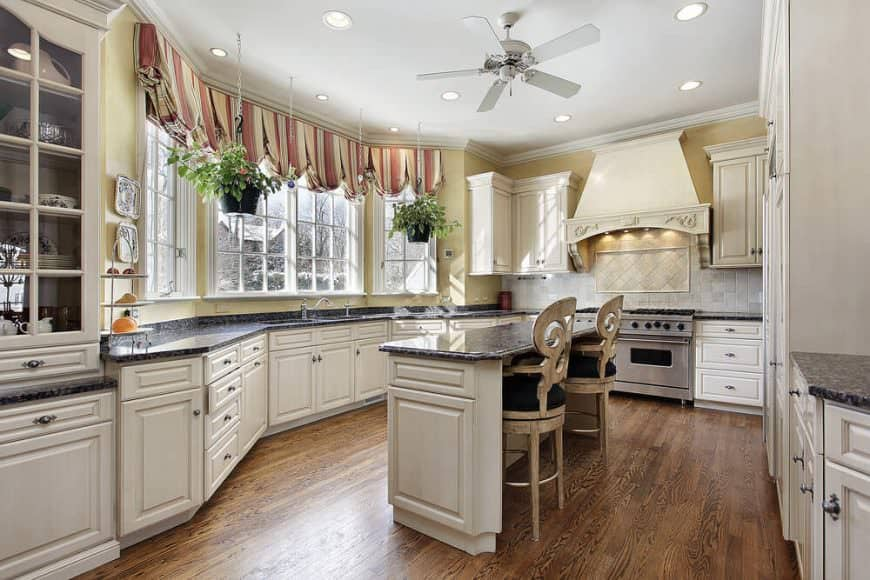 Kitchen features yellow walls with brick tiles backsplash, white cabinets, hardwood floors and a ceiling fan hung over a white island table topped with black marble countertop seating a pair of wooden with black cushion chairs.