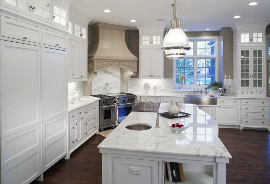 Kitchen with white cabinets, hardwood flooring, big pendant lights, island table with marble countertop and stainless stove with dual ovens and a nice vent hood.