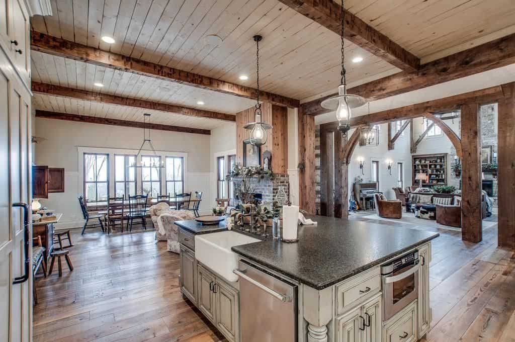 A farmhouse kitchen with a rustic touch. It has two pendant lights hanging on a wood beam ceiling and an island table with white wooden cabinets.