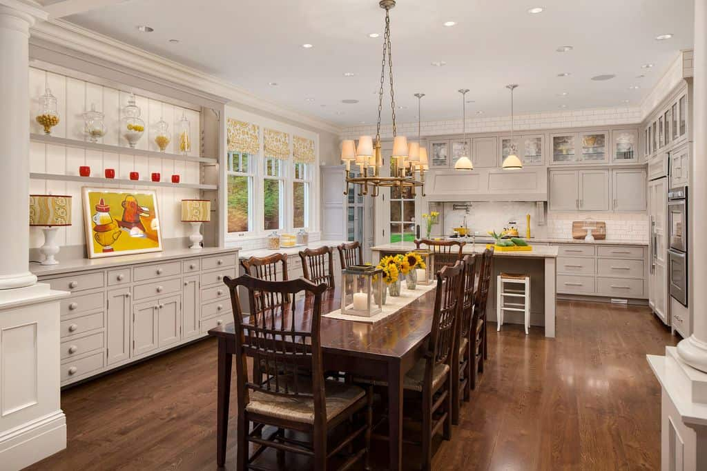 Lovely kitchen with hardwood flooring, white brick walls, gray wooden cabinets, an island table with chairs and classic pendant lights.