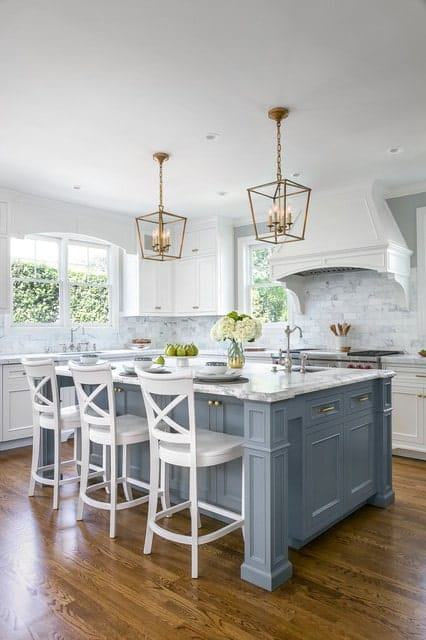 Stunning kitchen features brick tiles backsplash, white cabinets and hardwood flooring, Two industrial chandeliers hung over a dusty blue breakfast island topped with white marble and lined with three white wooden chairs.