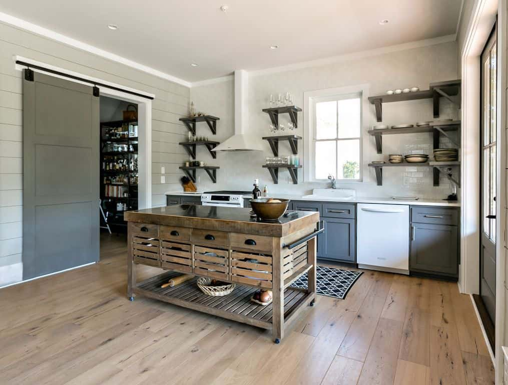 Gray and white kitchen with a rustic breakfast island, gray wooden cabinets and shelves, white brick walls, black printed kitchen rug and hardwood flooring.