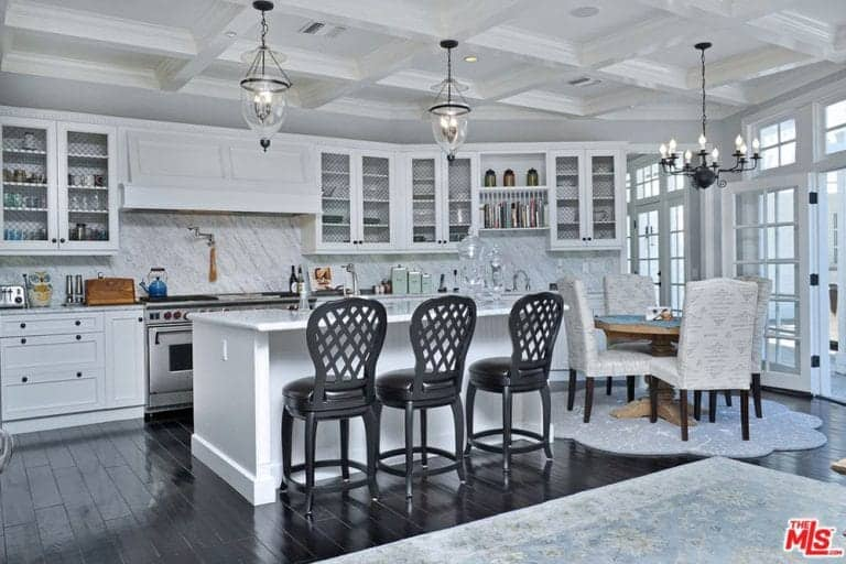 White with a touch of black kitchen with glass pendant lights hanging on a coffered ceiling, marble backsplash, white cabinets, black hardwood floors and a breakfast island with three black chairs.