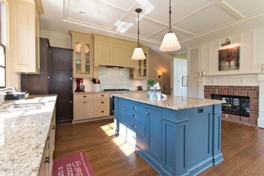 Kitchen with blue island table and a marble countertop, wooden cabinets, hardwood flooring and umbrella pendant lights hanging on a coffered ceiling.