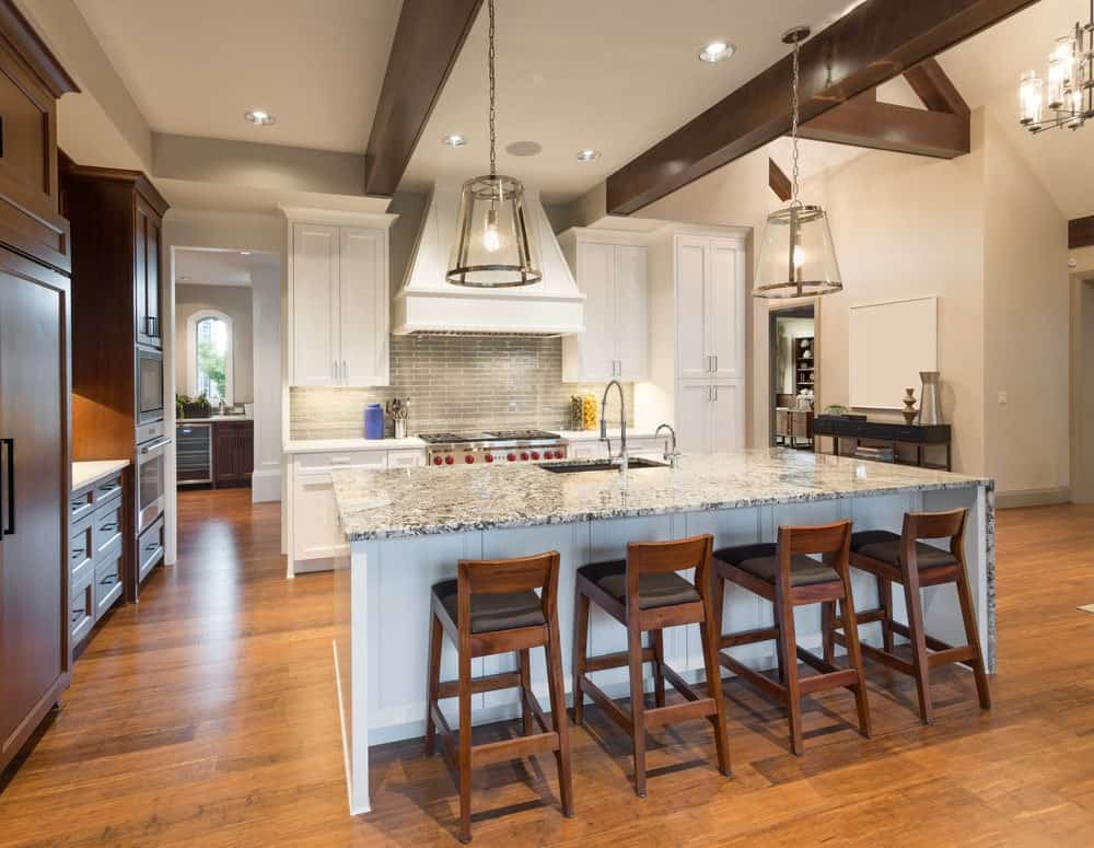 Kitchen with white and brown cabinets, hardwood flooring, gray backsplash, island table with gray marble countertop and wooden chairs and two huge pendant lights hanging on an exposed wood beam ceiling.