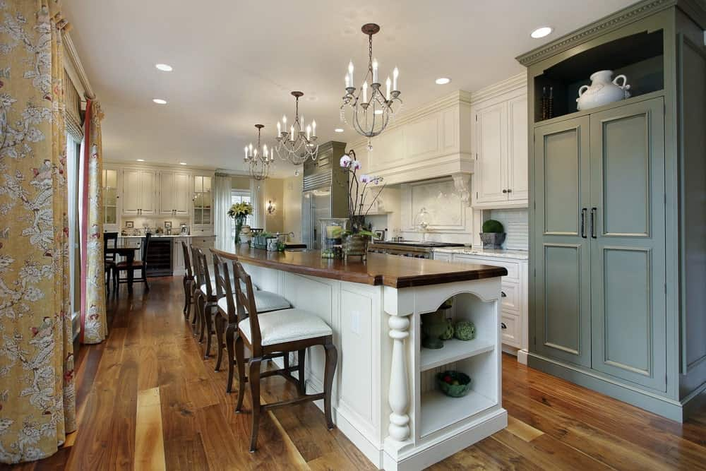 Long wooden island table with chairs, white and gray cabinets, hardwood flooring and a crystal candle chandelier adding elegance to this kitchen.
