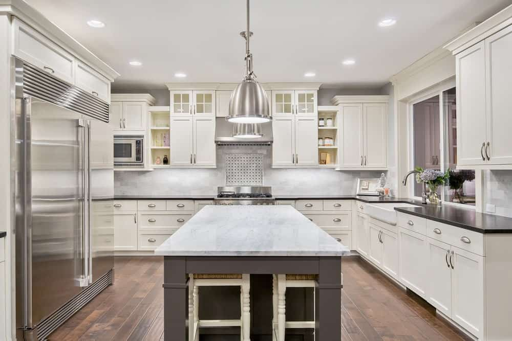 Modern kitchen with hardwood flooring, white cabinets, stainless steel appliances,  an island table with marble countertop and two aluminum pendant lights.