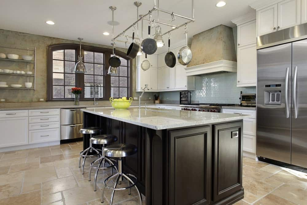 Kitchen with tiled floors, white cabinets, blue backsplash, huge fridge, an island table with dark brown cabinets and marble countertop, aluminum chairs and hanging steel bars for holding cookwares.