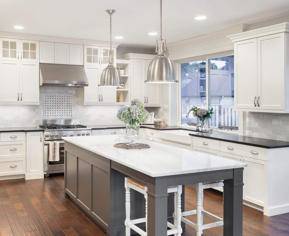Clean white kitchen with hardwood flooring, gray island table with white marble countertop, two pullout chairs and two aluminum pendant lights.