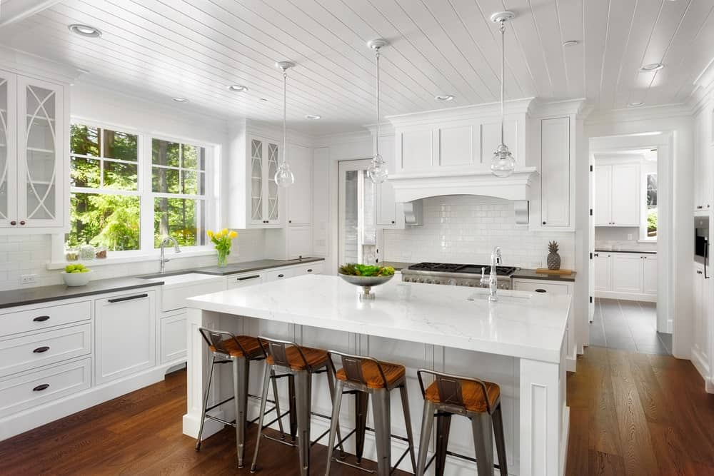 Fresh kitchen with white cabinets, brick backsplash, hardwood flooring, white island table with chairs and white ceiling with hanging glass pendant lights.