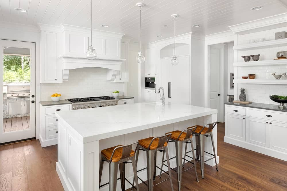 Charming white kitchen with wooden cabinets, breakfast island with marble countertop, wood designed chairs, hardwood flooring and globe pendant lights.