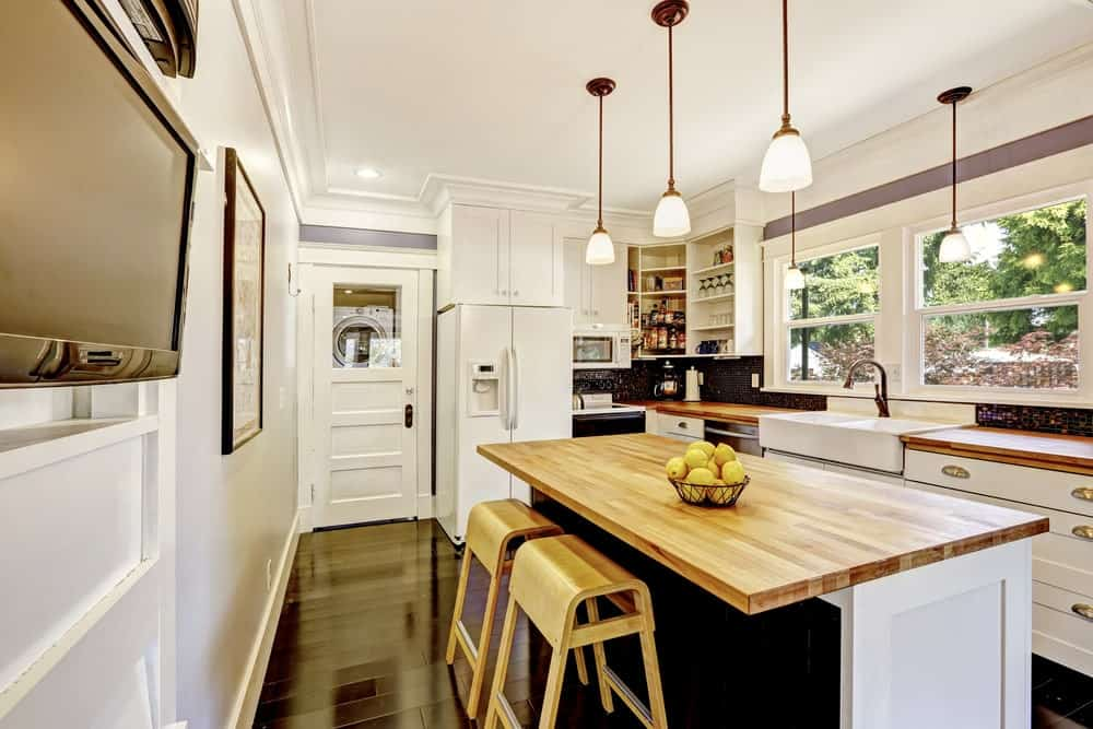 Kitchen with black hardwood floors, white walls with an accent of purple color, breakfast island with wooden countertop and wooden chairs, a wall frame and classic pendant lights.