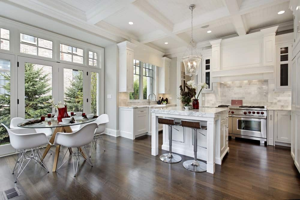 Kitchen with hardwood flooring, white cabinets, an island table with marble countertop and two bar stools, white brick backsplash and an elegant pendant lighting hanging on a coffered ceiling.