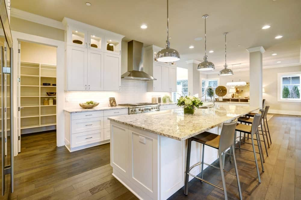 A wide kitchen with gray walls, white cabinets, hardwood floors, long breakfast table with gray marble countertop and bar stools and aluminum pendant lights.