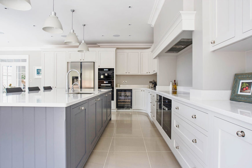 Beautiful cottage kitchen painted with muted gray walls. It features white cabinets, tiled floors and three pendant lights hung over a dusty blue breakfast island topped with white marble.