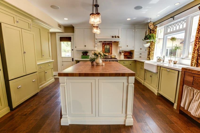 Simple kitchen with hardwood flooring, white and olive green cabinets, a wooden island table and a glass pendant lights.