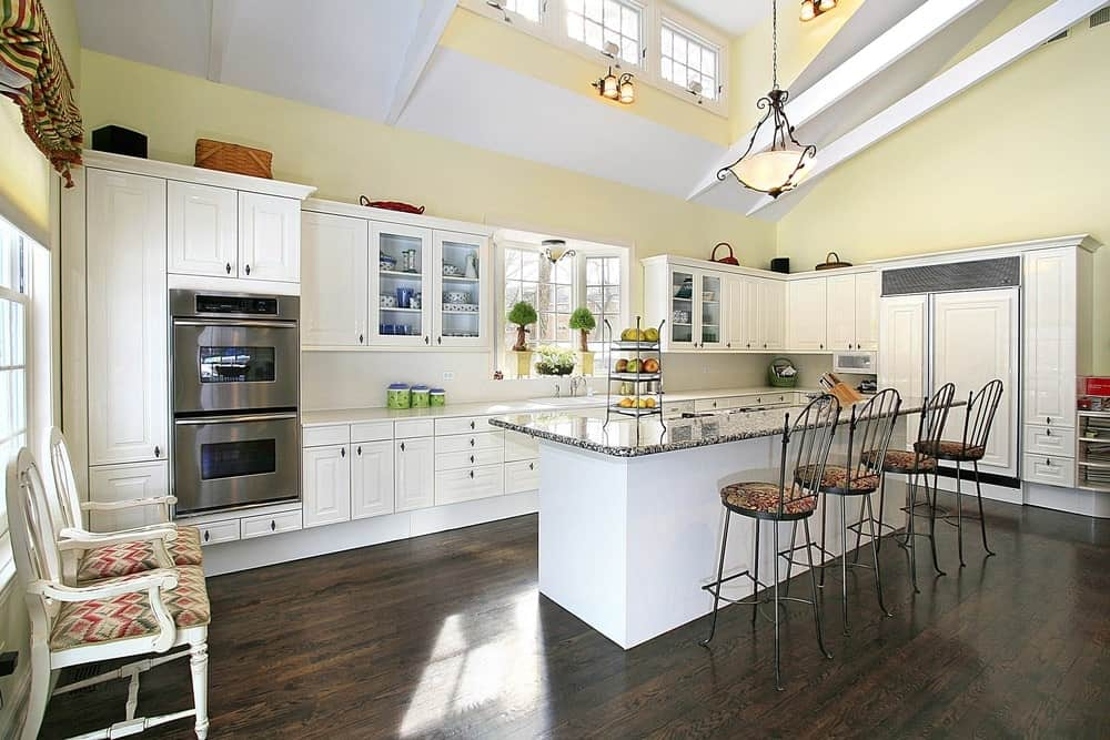 Bright kitchen with yellow walls, hardwood flooring, white cabinets, rectangular island table with chairs and vintage pendant light.