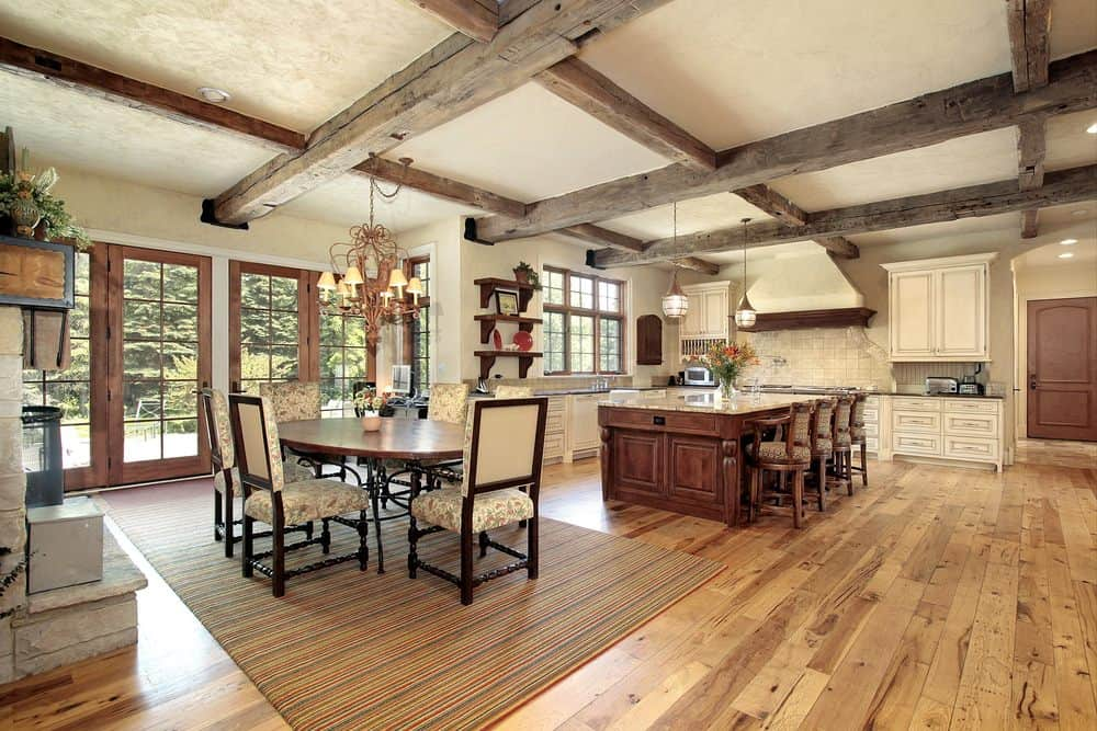 Rustic woody kitchen with white cabinets, hardwood flooring, an island table with chairs and a globe pendant light hanging on a wood beam ceiling.