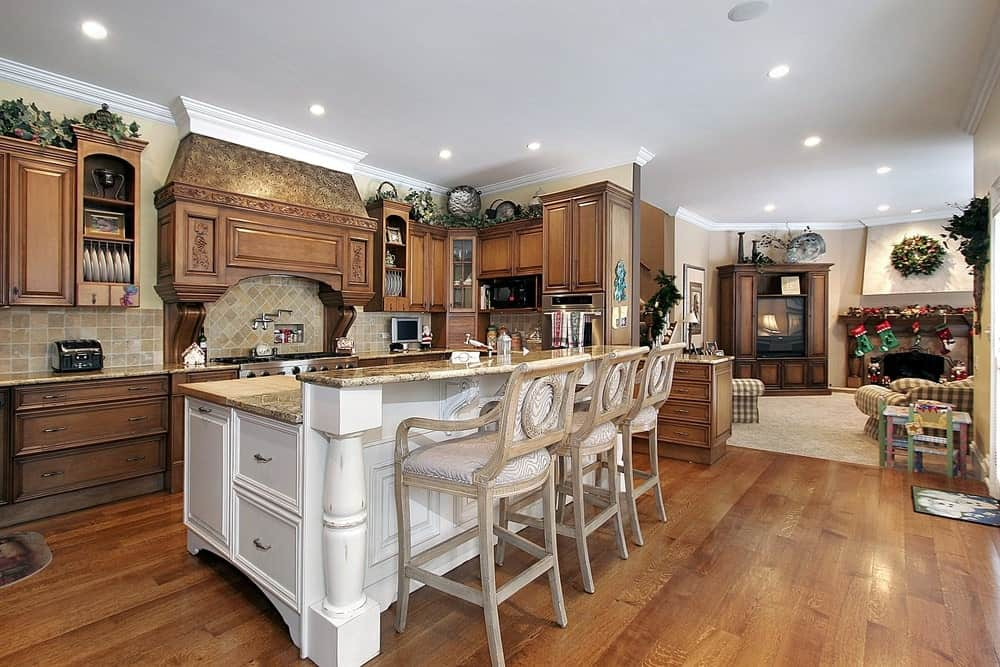 Classic kitchen with wooden cabinets and shelves, hardwood flooring, and a breakfast island with white cabinets and chairs.
