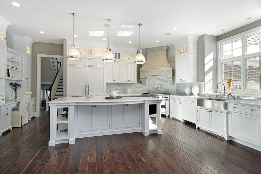A classic white kitchen with wooden cabinets, an island table with marble countertop, pendant lights and a hardwood flooring contrasting the white elements.