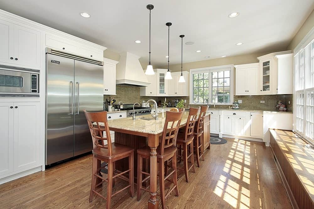 A kitchen with hardwood flooring, white cabinets, glass windows, breakfast island table with marble countertop and wooden chairs and classic pendant lights.
