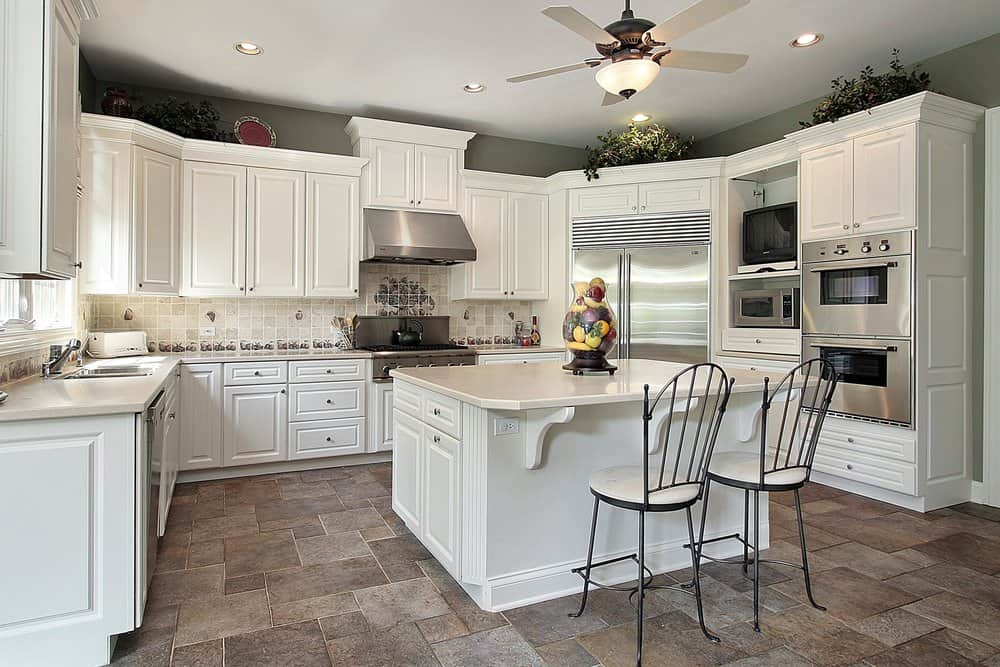 White kitchen with wooden cabinets, tiled floors, kitchen island with two chairs and a ceiling fan with lights.