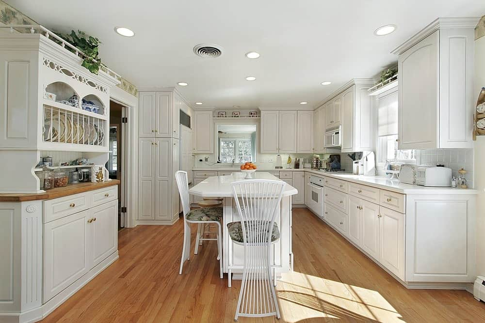 Wide kitchen with white wooden cabinets, hardwood flooring and white breakfast island with chairs.
