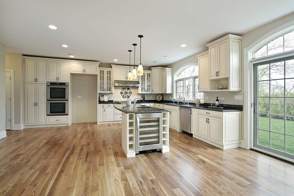 Spacious L-shaped kitchen with hardwood flooring, white wooden cabinets, an island table with black marble countertop and white wooden cabinet with shelves, classic pendant lights and arched windows and door.