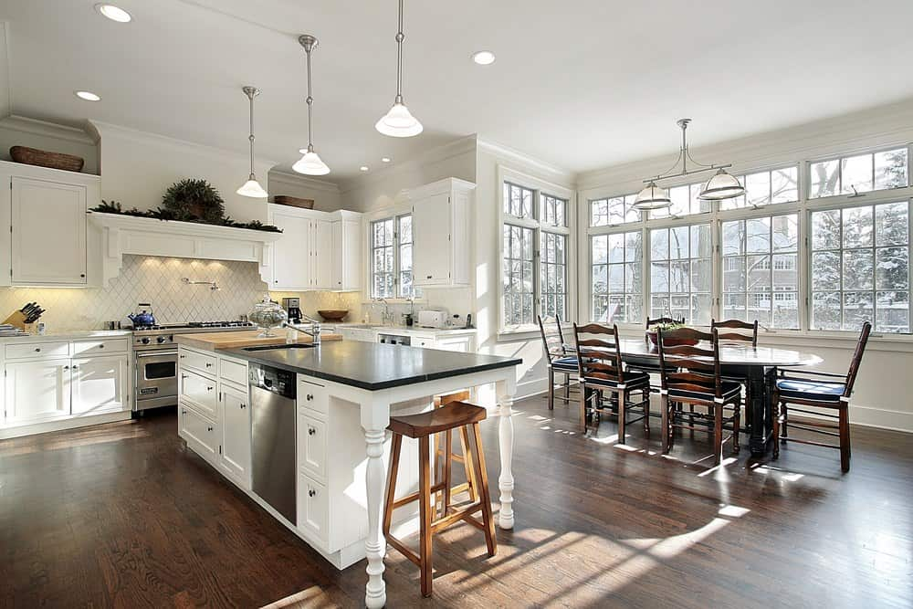 Simple kitchen with white wooden cabinets, a diamond patterned white backsplash, silver pendant lights and a kitchen island with sink, white cabinets and a wooden chair.