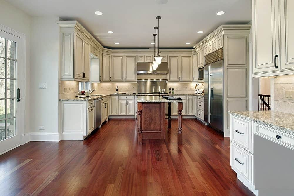 Wide kitchen with hardwood flooring, wooden cabinets, vintage pendant lights, an island table and stainless steel appliances.