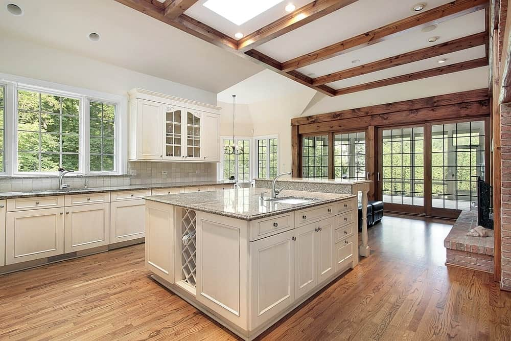White kitchen with wooden tones, a breakfast island with sink and a gray marble countertop, white cabinets, hardwood floors, wood beam ceiling and a kitchen bar.