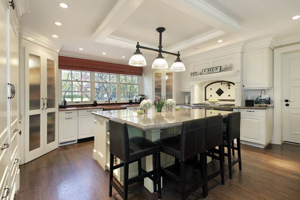 A kitchen with hardwood flooring, white wooden cabinets, breakfast island with gray marble countertop and black cushioned chairs and a classic pendant lights hanging on a tray ceiling.